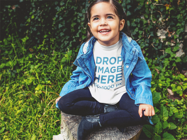 Little Girl Wearing a Denim Jacket and T-Shirt Mockup in the Garden a12098