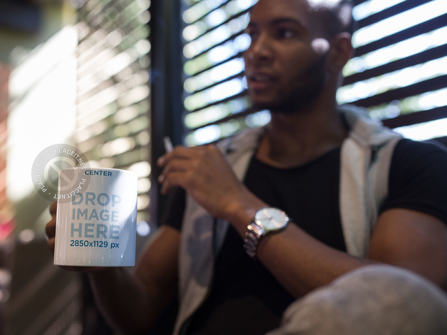 Man at a Coffee Shop Holding a Mug Mockup a12298