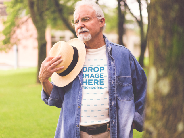 Mockup of an Elder Man Wearing Round Neck Tee with a Denim Sleeve Shirt Outdoors a12391