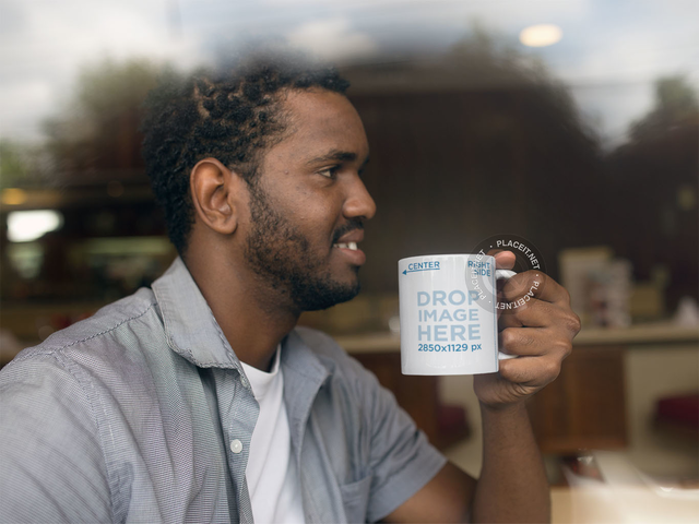 Young Man at a Coffee Shop Holding his Mug Mockup a12325