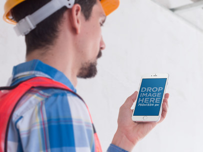 White iPhone 6 Mockup Held by a Construction Worker in Portrait Position a12427