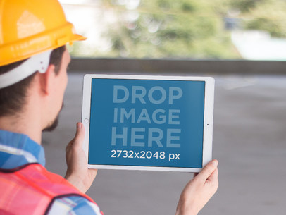 iPad Pro Mockup Held in Landscape Position by a Construction Worker a12431wide