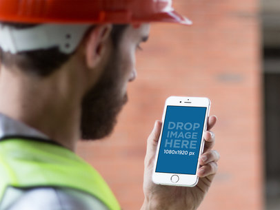 White iPhone 6 Plus Mockup of a Construction Worker Checking his Phone a12418