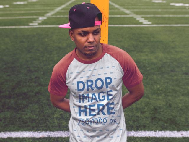Raglan T-Shirt of a Black Man Wearing a Snapback Hat in a Field a12468