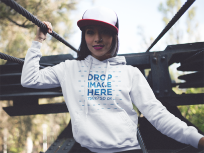 Hoodie Mockup of a Young Woman Wearing a Hat Outdoors a12481