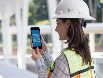 Female Construction Worker Holding an iPhone 6 Plus Mockup a12576