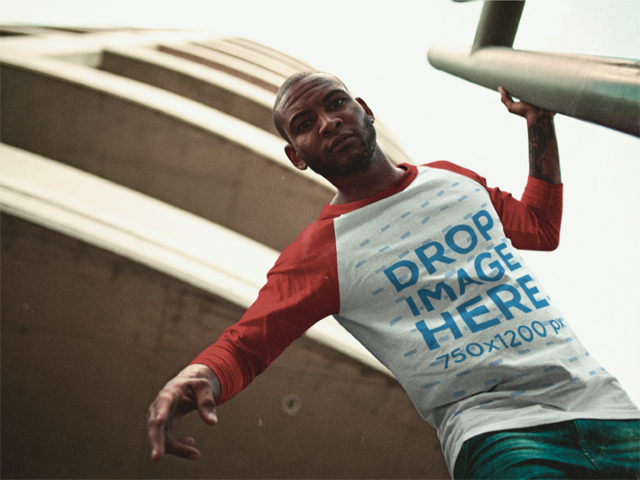Young Black Man Wearing a Raglan Tee Mockup While Looking Down Near a Building a12562