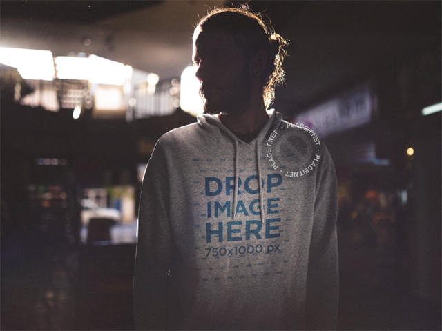 Hoodie Mockup of a Young Man with Long Hair Standing in the Dark b12625