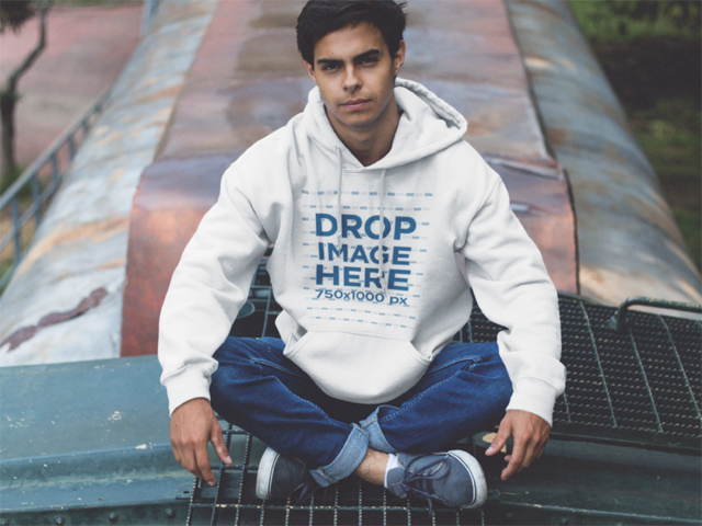 Young Man Sitting Cross-Legged on a Train Pullover Hoodie Mockup a12497