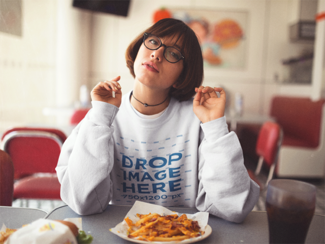 Crewneck Mockup of a Trendy Girl with Short Hair and Glasses Eating Fries at a Diner a12657