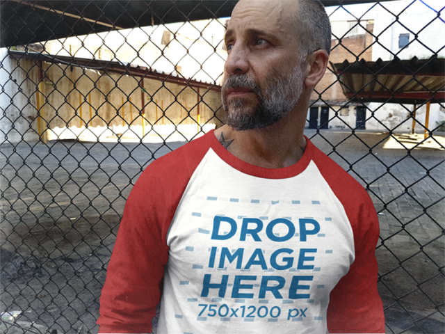 Middle-Aged White Man Staring Away and Leaning Against a Rusty Fence Raglan Tee Mockup b12613