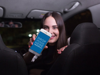 Woman in the Front Seat of a Car Holding a White iPhone 7 Mockup in Portrait Position Mockup a12802wide