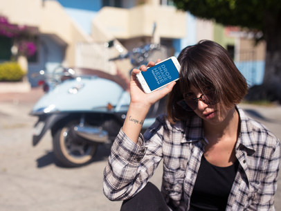 Mockup of a White iPhone 6s Held by a Young Woman with a Vespa Scooter a12954wideb