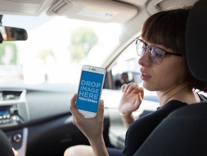 Hipster Girl Riding in the Passenger's Seat of a Car Checking her iPhone 6 Mockup a12941wide
