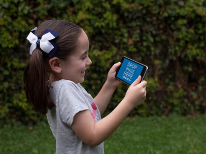 Little Girl Playing on her Black iPhone 7 Plus in Landscape Position Mockup in the Back Yard a13003wide