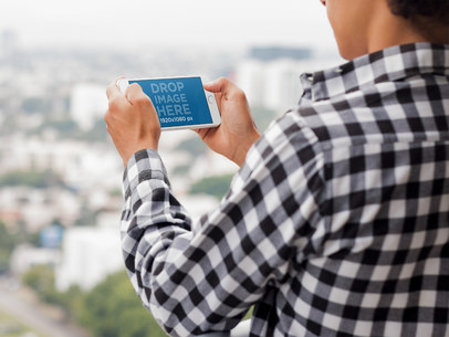 Young Man Playing on his White iPhone 7 Plus Mockup in Landscape Position at his Apartment Balcony a13040w