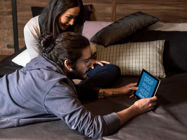 Mockup of a Couple Playing with a Black iPad in Landscape View in their Bedroom a13100