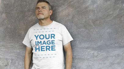 Middle Aged Hispanic Leaning Against a Black Wall Wearing a T-Shirt Video Mockup a12746