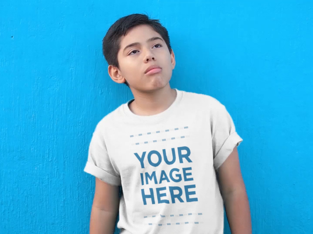 Kid's T-Shirt Video Mockup of a Young Boy Chewing Bubblegum in Front of a Blue Wall a12771