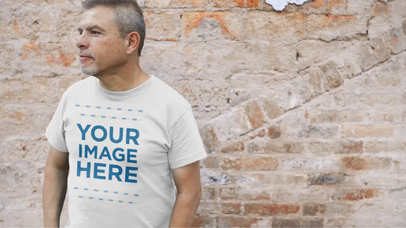 Middle Aged Man Standing Near an Old Brick Wall Wearing a Simple T-Shirt Video Mockup a12748