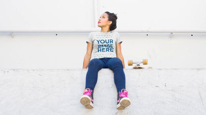 Young Skater Girl Sitting on a Ledge and Chewing Gum T-Shirt Video Mockup a12830