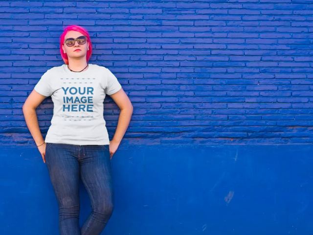 T-Shirt Video Mockup Featuring a Plus Size Girl with Pink Hair Wearing a Round Neck Tee and Leaning Against a Bright Blue Wall a12651