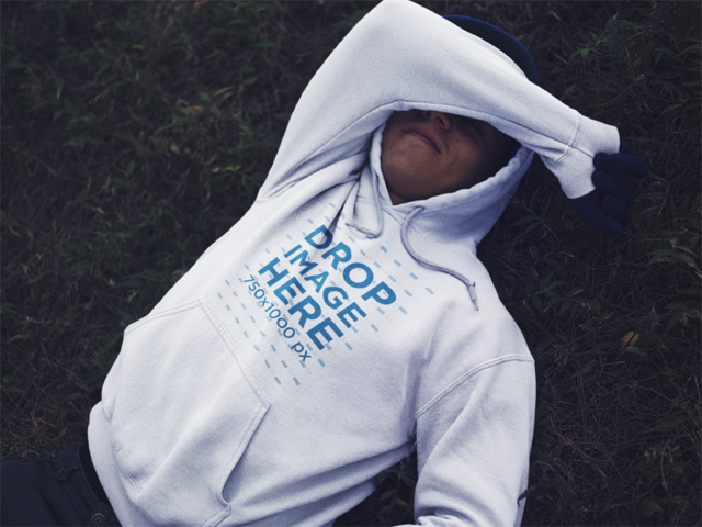 Mockup of a Guy with a Hoodie Lying in the Grass with his Face Covered a13197