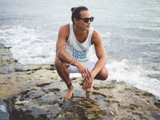 Surfer Guy Wearing a Tank Top Mockup and Sunglasses at a Rocky Shore a12728