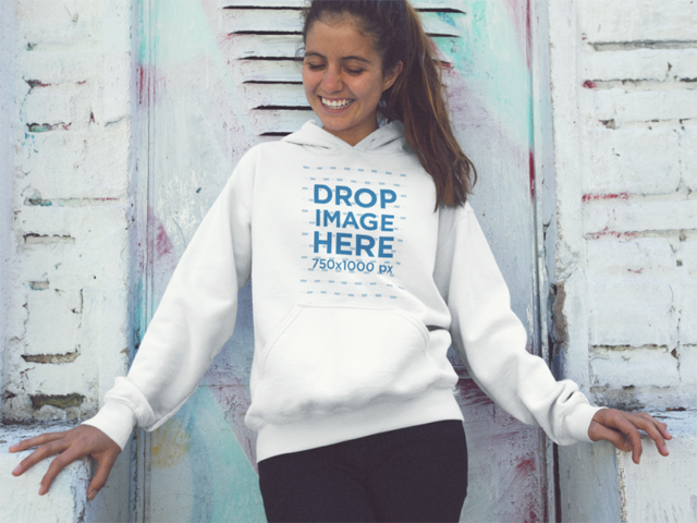 Smiling Young Girl Wearing a Pullover Hoodie Mockup Against a White Wall a12848