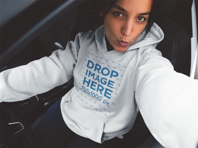 Young Woman in her Car Wearing a Pullover Hoodie and Taking a Selfie a12923