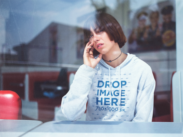 Hoodie Mockup Featuring a Young Woman Sitting Inside a Café Looking Out a Window a12677