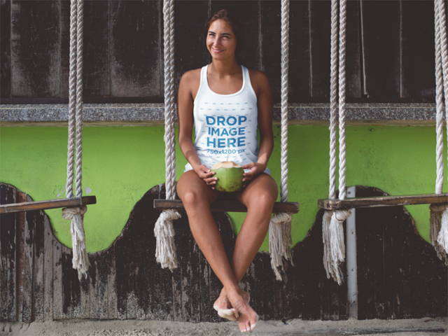 Lovely Beach Girl Wearing a Tank Top While Having a Coconut on a Swing a12734