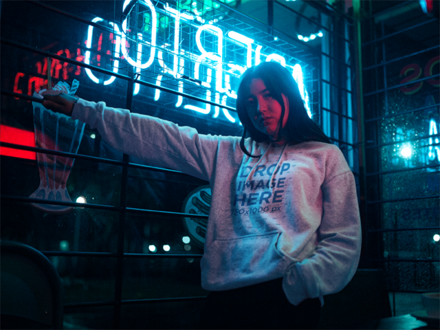 Mockup of an Asian Woman Wearing a Pullover Hoodie Near Neon Lights a12715