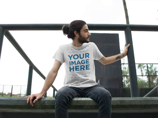Guy with Long Hair and a Beard Sitting on a Ledge Wearing a Round Neck Tee Video Mockup a12977
