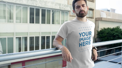 Hipster Guy with a Beard Leaning on a Rail Wearing a Round Neck T-Shirt Video Mockup a12172