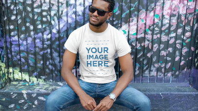 T-Shirt Video Mockup of a Young Black Man Wearing Sunglasses Sitting Near a Painted Wall a12116-121916