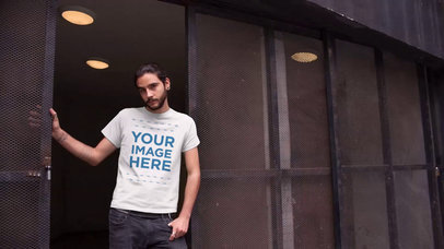 Hipster Guy Leaning at the Entrance of an Urban Building T-Shirt Video Mockup a12976