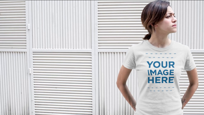 Young Woman Standing Near a White Wall Wearing a Round Neck T-Shirt Video Mockup a12148-121916