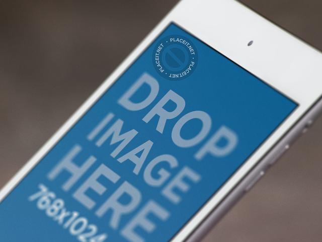 Close Up Mockup of a Blurred White iPad Mini Against a Blurry Background b12760