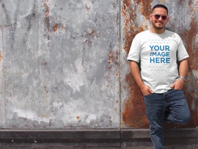 Plus Size T-Shirt Video Mockup Featuring a Cool Guy Leaning Against a Rusty Wall a12465-122016