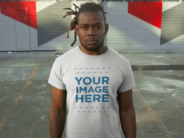 Young Man With Dreadlocks Standing in a Parking Lot Wearing a Round Neck Tee Video Mockup a12237-122016