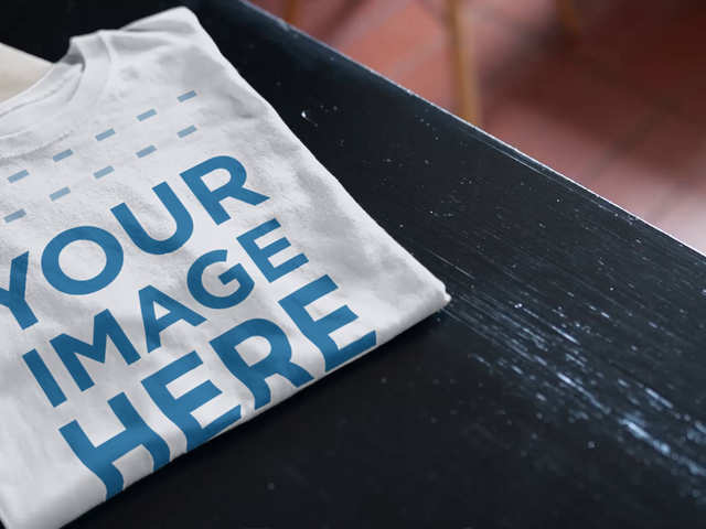 Folded T-Shirt Mockup Video Over a Dark Wooden Table a13132-122316