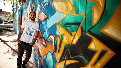 Hipster Guy with a Man Bun Leaning on a Graffiti Wall Wearing a T-Shirt Mockup Video a13214-122616
