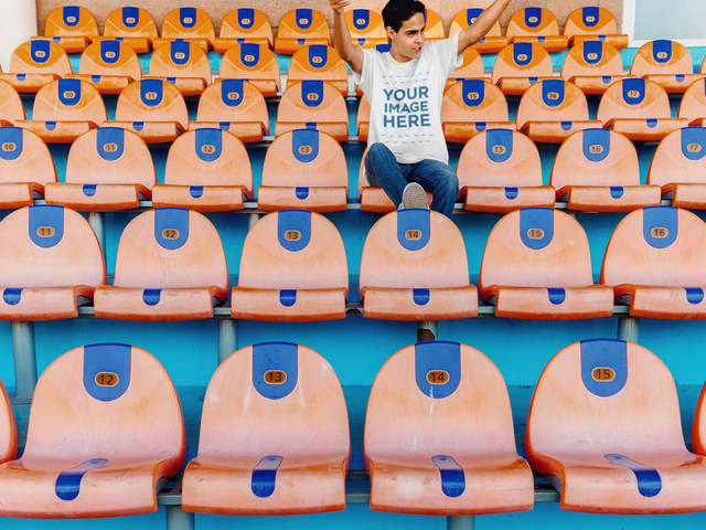 T-Shirt Mockup Video of a Young Man Sitting in the Stadium Bleachers Cheering a13227-122616