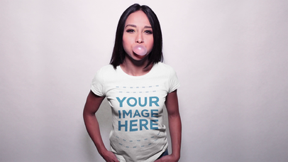 Young Woman Wearing a T-Shirt Mockup Video While Blowing Bubble Gum a13156-122716