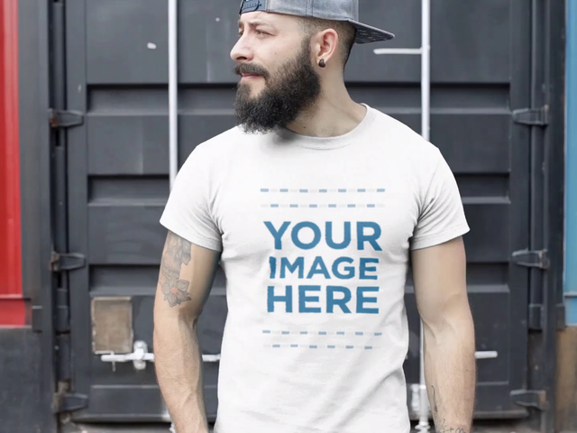 Video Mockup of a Tattooed Guy Wearing a Hat and Round Neck Tee in a Container Yard a12263-122816