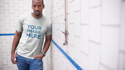 Black Man Lying Against a Wall Wearing a T-Shirt Video Mockup a13121
