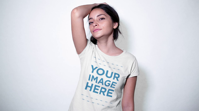 Trendy Girl Wearing a T-Shirt Against a White Wall Video Mockup a13363