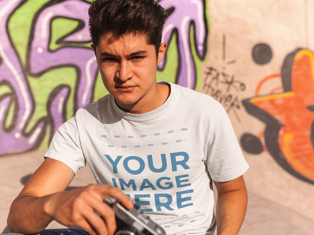 Young Man With a Vintage Camera Wearing a T-Shirt at a Skating Park Mockup Video a13503
