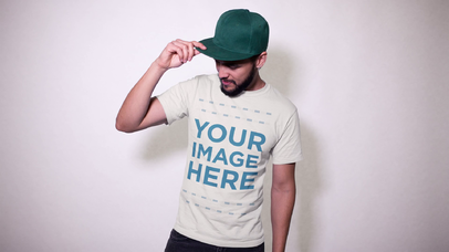 Trendy Guy With Beard Wearing a T-Shirt and a Trucker Hat Against a White Wall Stop Motion Mockup a13473